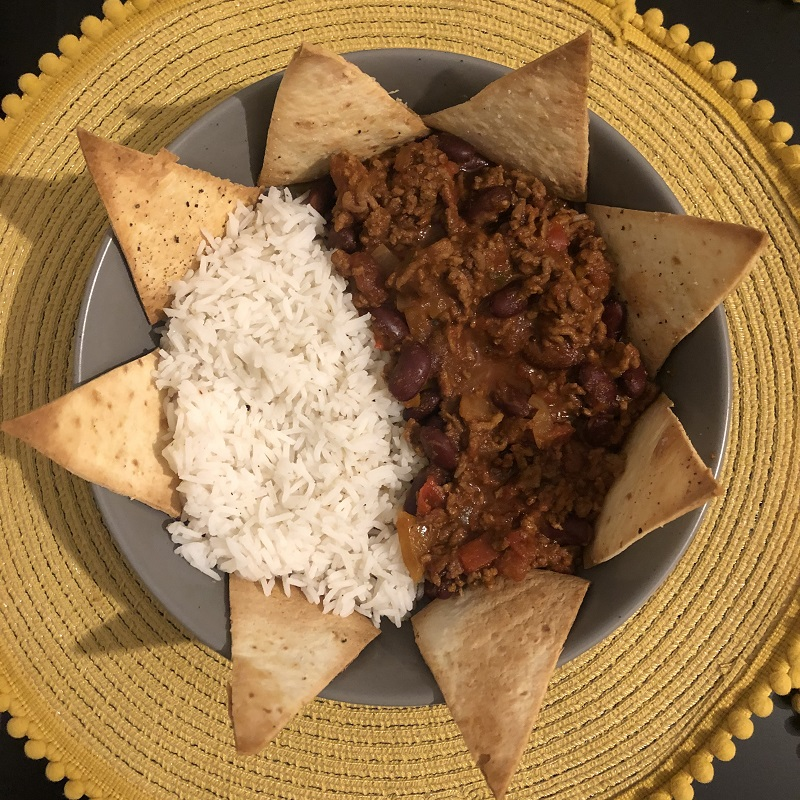 Photo of Zoe's cooking a meal of chilli and rice decoratively placed on a plate with nacho crisps around the meal